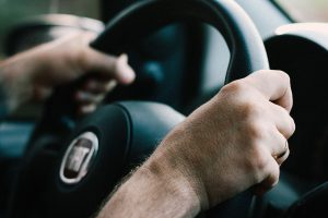 photo of a man with hands on steering wheel of car