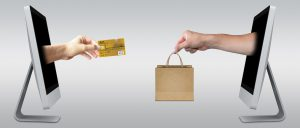 two computer screens with hands coming out of both doing a sales transaction with credit card and shopping bag