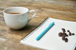 image of cup of coffee and a notebook with pen on top of it