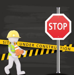 stop sign and a cartoon character of man carrying cones with a sign saying Site is under construction