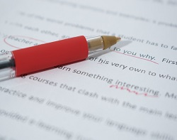 paper and pen correcting spelling mistake