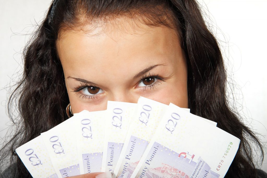 woman holding banknotes spread across her face