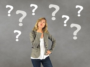 Woman looking puzzled with question marks around her