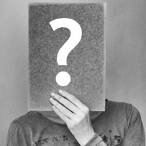 A person holding a piece of paper in front of their face with a question mark on it. Hiding their face to be annonymous