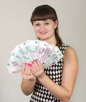 Young lady holding fanned bank notes in her hands