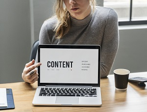 woman pointing to pc screen with the word content on the screen