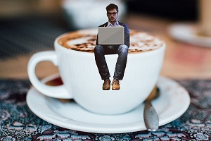 man working on a pc sitting on top of a coffee cup